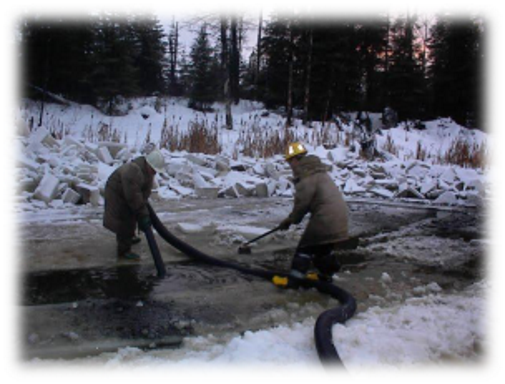 2 workers pumping tailings from pond in winter