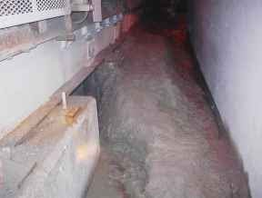 mudded out walkway beside a conveyor in an underground mine