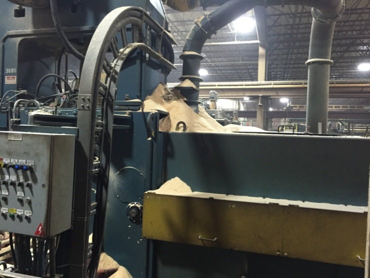 inside sawmill warehouse with woodchips on equipment