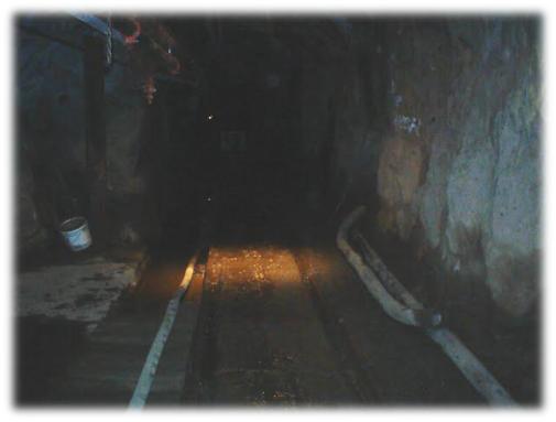 underground mine tunnel with industrial hose on ground