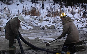 workers using industrial vacuum for tailings recovery in pond
