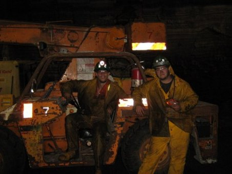 underground miners in scoop tram